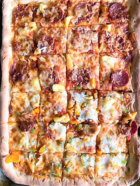 Overhead shot of full sheet pan pizza topped with pepperoni, pineapple, and peppers, cut into 24 square slices.