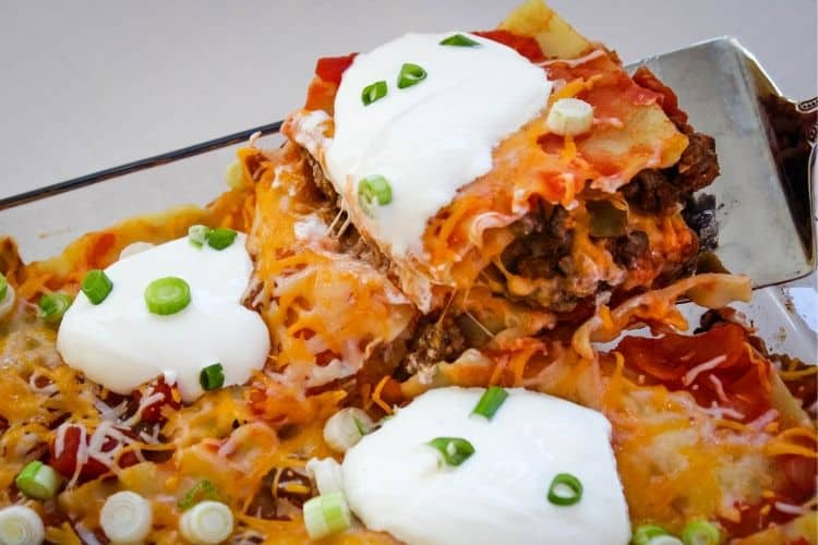 slice of taco lasagna topped with sour cream