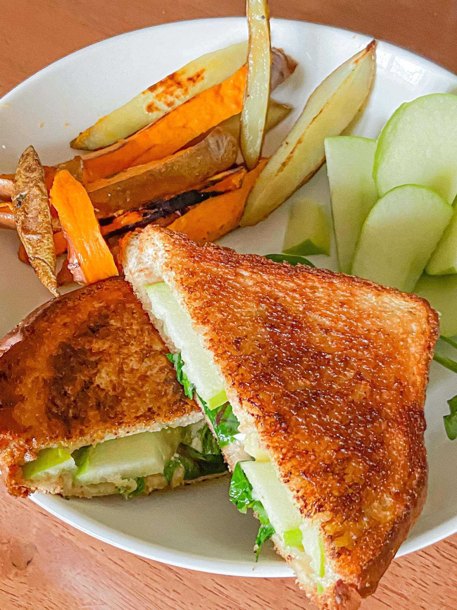 Closeup of goat cheese apple grilled cheese with sweet potato wedges and apple slices