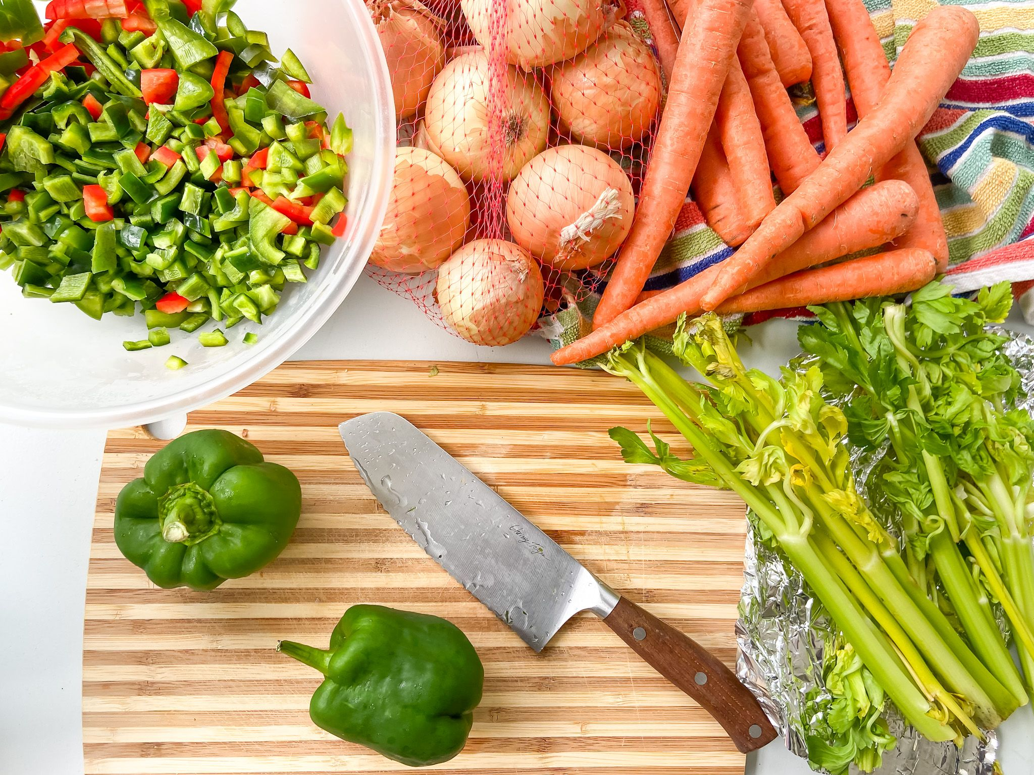 cut up peppers, bag of onions, raw carrots and celery, cutting board, easy freezer meal soup starters