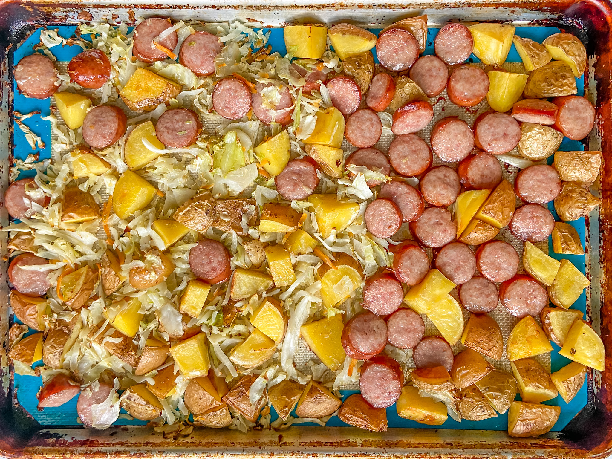 sheet pan meal with cooked kielbasa, potatoes, shredded cabbage